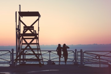 Photo of two women standing near the ocean at sunset