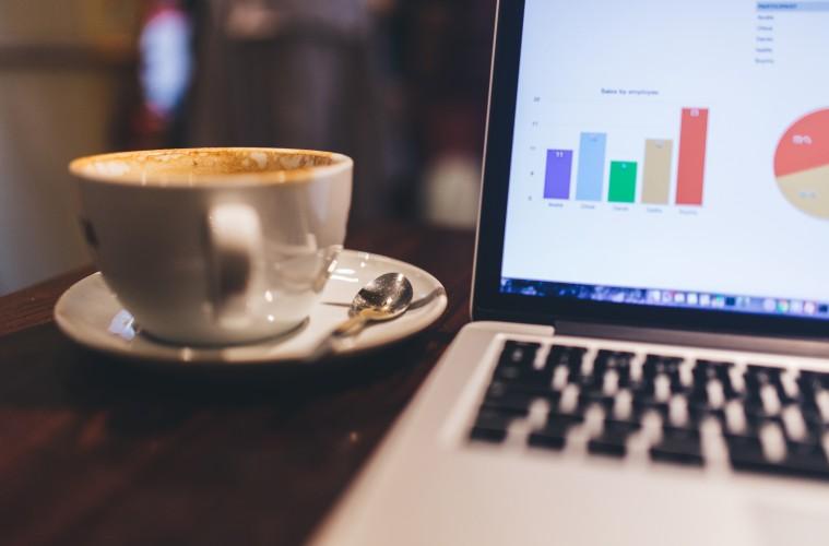 Coffee alongside laptop