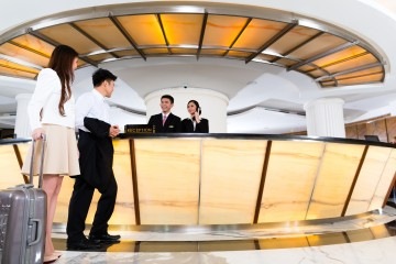 Asian Chinese woman and man arriving at front desk or reception of luxury hotel in business clothes with trolley