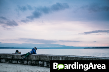 Boarding Area logo on a photo of two kids watching the sunset over water