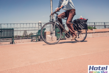 Hotel Interactive logo on a photo of a man bicycling on street
