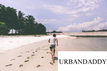 Urbandaddy logo on a photo of a boy running on the beach