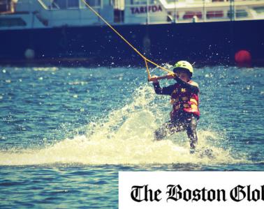 The Boston Globe logo on a photo of a boy waterskiing