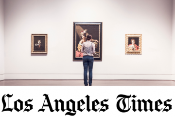 Los Angeles Times logo on a photo of a woman looking at portraits in an art gallery