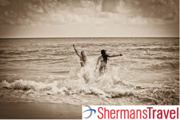 Shermans Travel logo on a photo of two women in the water near a beach