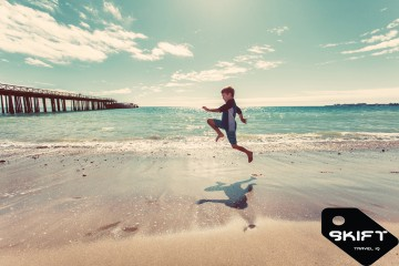 Skift logo on a photo of a boy running on the beach