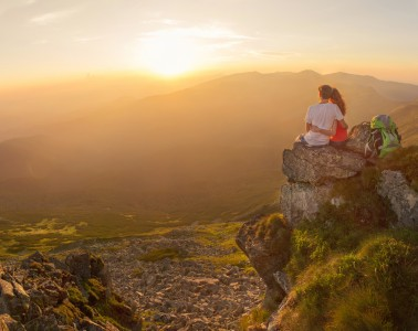 Happy couple feel freedom and enjoy the beautiful view in the mountains and looking on sunset