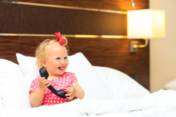 cute little girl taking on the phone in hotel room, kids travel