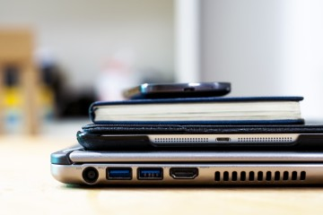 Laptop with several business devices stacked on top of it