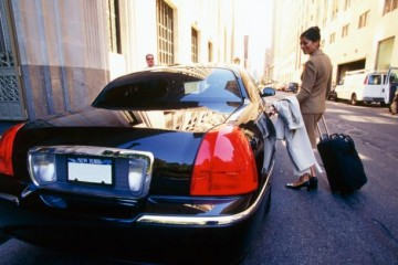 Photo of a businesswoman with a suitcase entering a car