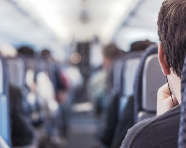 A man on an airplane listening to music with earphones