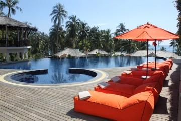 Pool chairs alongside a resort swimming pool