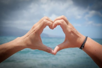 Man forming a heart shape with his hands with the ocean in the background