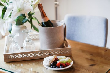 Champagne with glasses on a tray alongside a plate of fruit