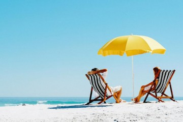 A couple relaxing with chairs and a parasol on the beach