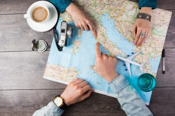 Two people planning a trip with a world map on a table