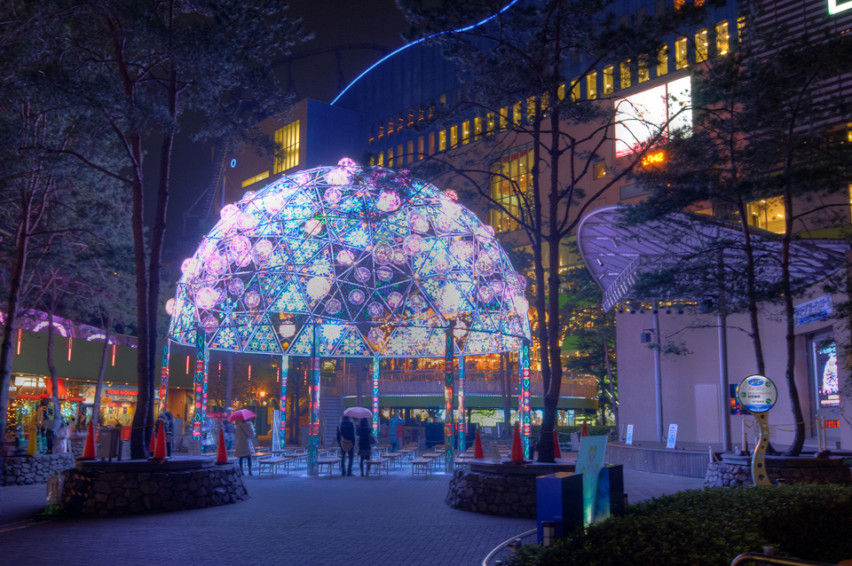 Bright fairy lights over dome in Tokyo public space.