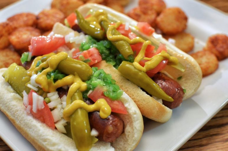 Two juicy chicago-style hot dogs with obligatory tator tots.