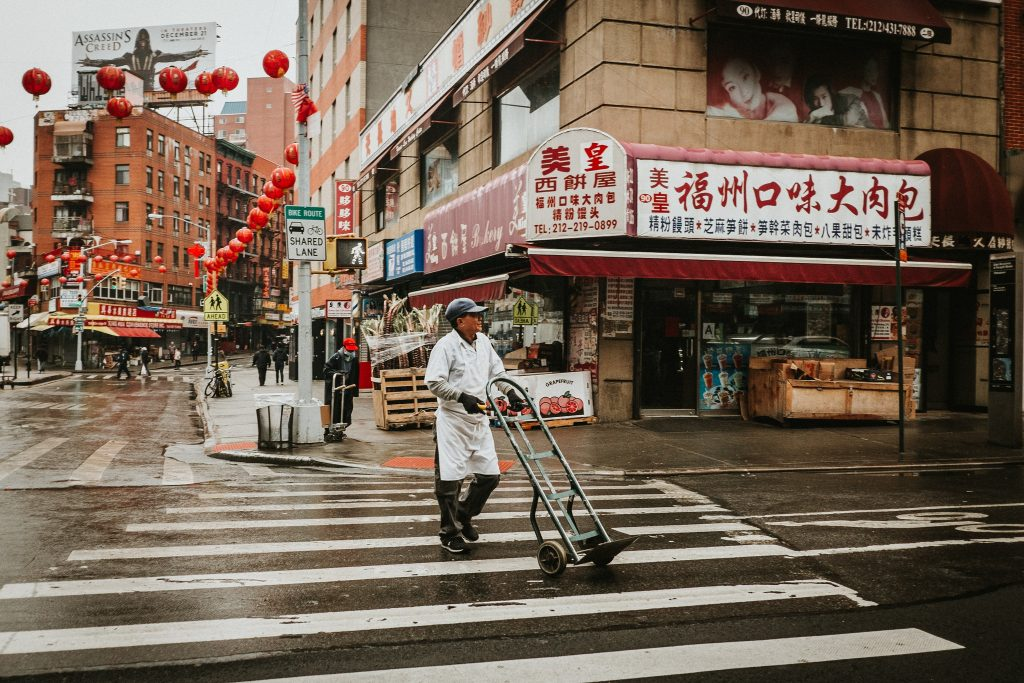 Man pushes dolly on rainy Monday in NYC's Chinatown
