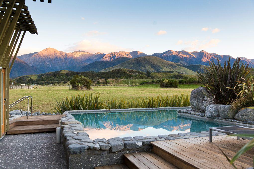 Jacuzzi overlooking calm green pasture and mountain backdrop.