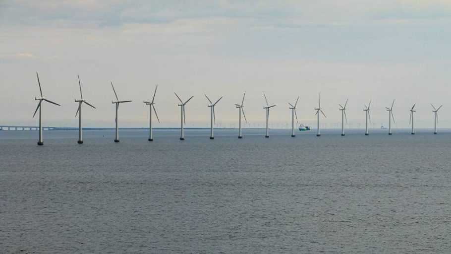 A danish offshore wind farm in Baltic Sea with ship passing in the distance.