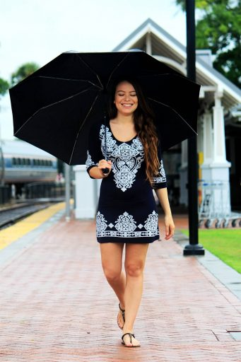 Woman in dress walking with umbrella on gray day.