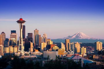 The iconic Space Needle and the rest of Seattle's downtown skyline with snow-capped mountains in the background.