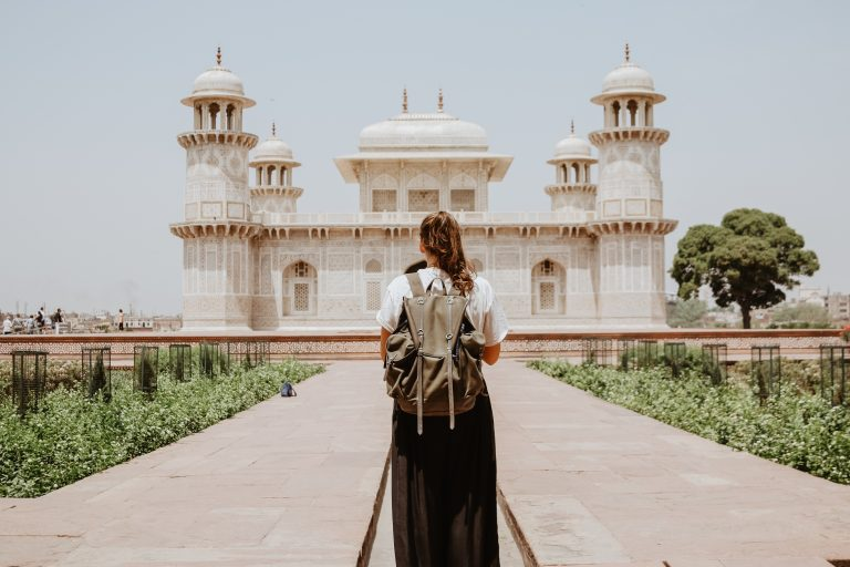 Solo traveler looks at Taj Mahal in Agra, India.