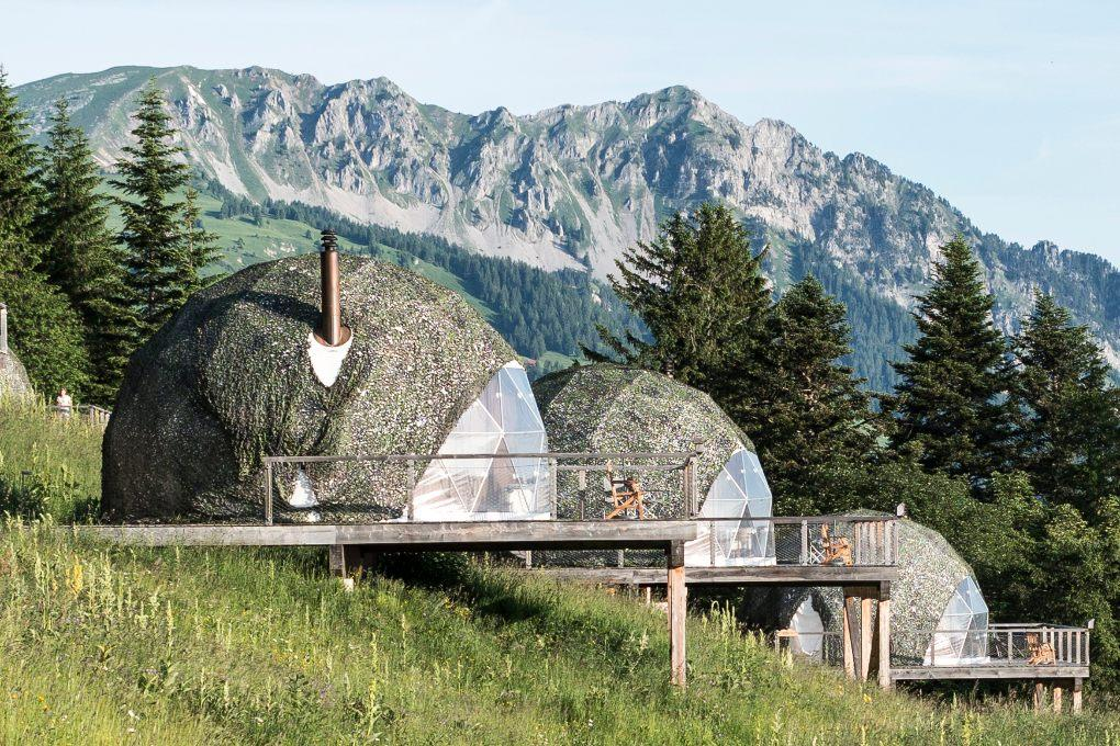 Three geodesic pods line a hillside with Swiss Alps in the background.