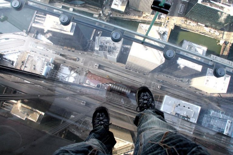 Waist-down view from Willis Tower sky deck looking straight over other Chicago high rises.