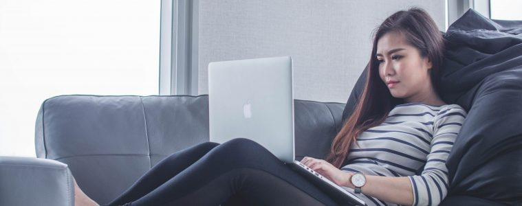 Woman lying on couch working on Macbook.