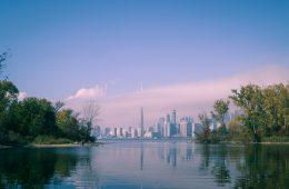 Abundant water and foliage give way to pink-blue sky and urban metropolis skyline.