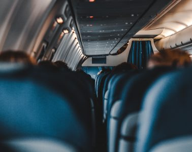 First-person view of airplane cabin as person ponders how to survive a long flight.