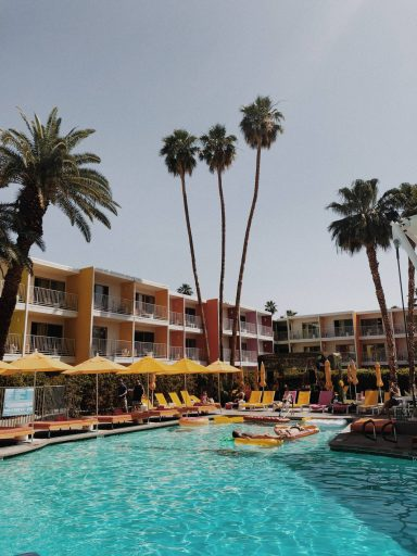 Stylish hotel with palm trees and a courtyard pool.