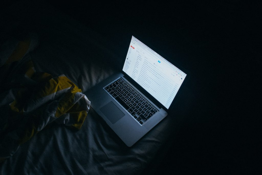 Laptop on bed at night showing emitting a blue screen and showing an email inbox.