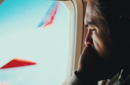 Man calmly looking out airplane window with face in palm.