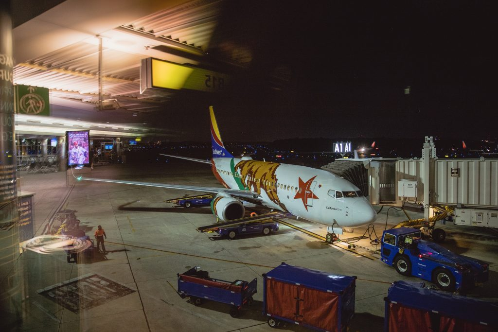 Airplane being unloaded on tarmac at night.