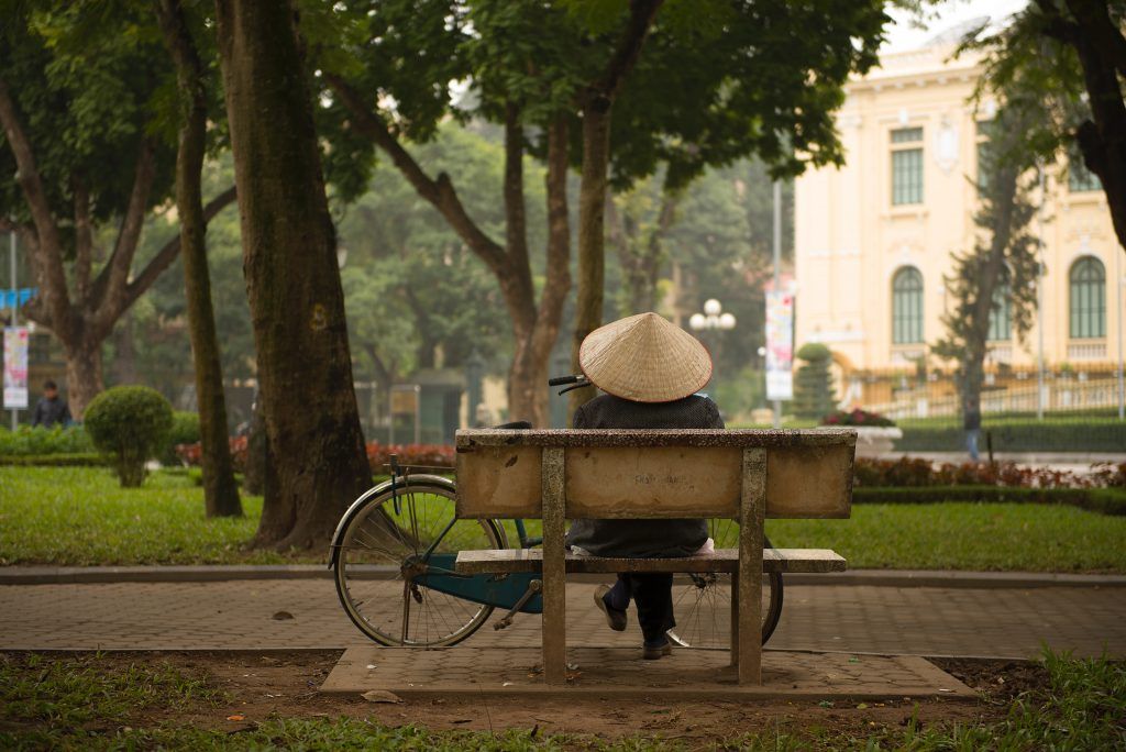 Person sits on bench in peaceful park in Hanoi, Vietnam