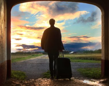 Man standing in door frame looking out at a vibrant setting sun over green field.