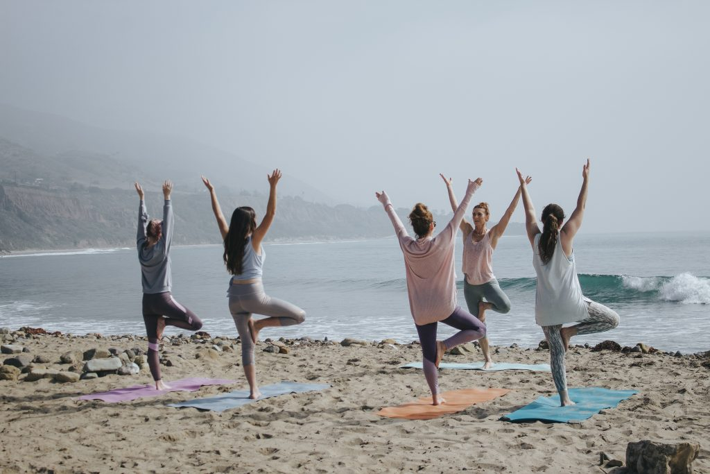 Ladies stand on left leg with arms stretched wide during a Mother's day yoga retreat on the beach.