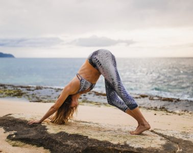 Woman stays in shape while traveling, doing downward dog yoga pose on beach under a glimmering overcast sky.