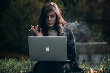 Woman sits on bench smoking cigarette with macbook on her lap.