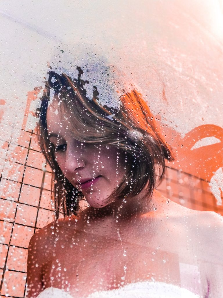 Woman peacefully staring down while showering with suds streaking on glass.