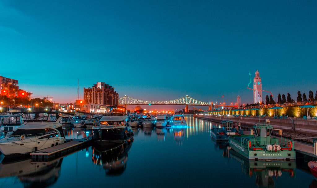 The Old Port of Montreal lit up against a blue sky evening.