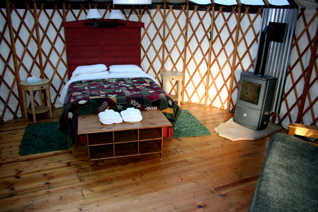 Cozy yurt interior with double bed and fireplace.