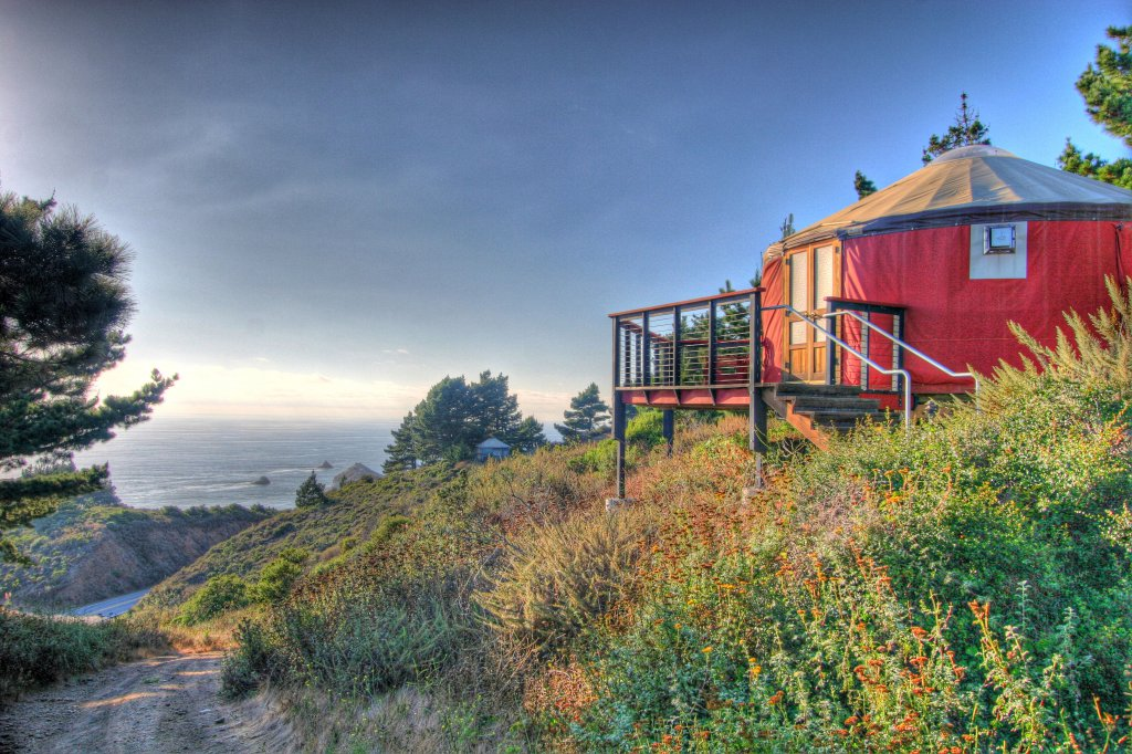 Red yurt overlooking trail, succulents and the Pacific Ocean.